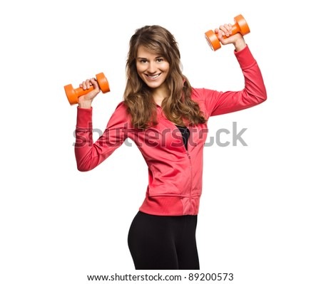 Beautiful and very athletically fit woman curls dumbbells with a winning smile. - stock photo