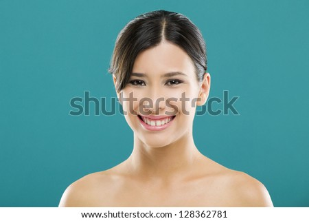 Beautiful and young asian woman smiling, over a blue background - stock photo
