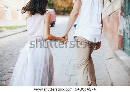 beautiful and young boy and girl walking down the street
