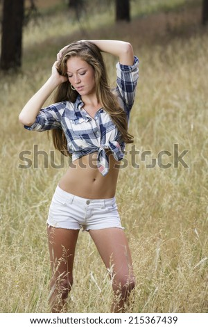 beautiful and young country girl posing outdoors in white shorts and flannel shirt - stock photo