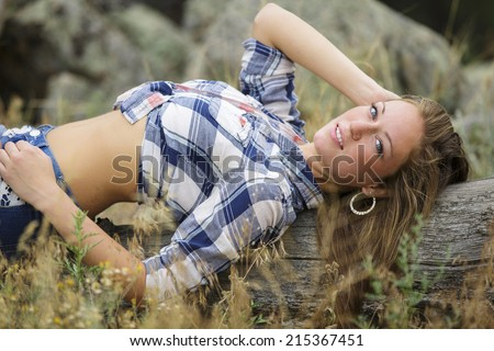 Beautiful and young girl laying on the ground and posing in blue flannel shirt with a sassy smile - stock photo