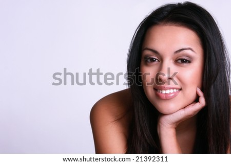 beautiful and young hispanic woman resting her head on her hand.