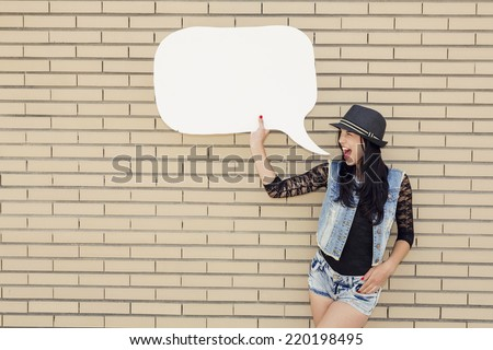 Beautiful and young teenager holding a thought balloon, in front of a brick wall - stock photo