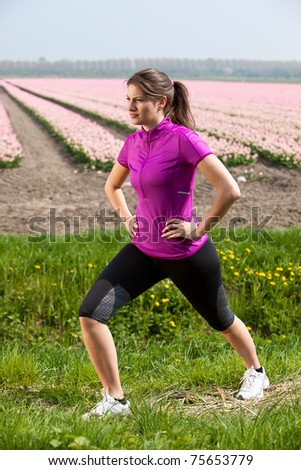 Beautiful and young woman doing stretch exercises outdoors - stock photo