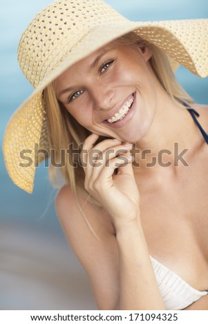 Beautiful and young woman in hat on a sunny day smiles for the camera - stock photo