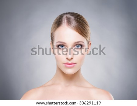 Beautiful and young woman over the grey background. Healthy skin. - stock photo