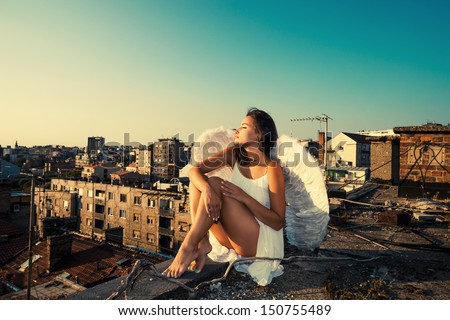 beautiful angel woman with white wings and white dress sit on the edge on roof enjoy in sunset over Belgrade - stock photo