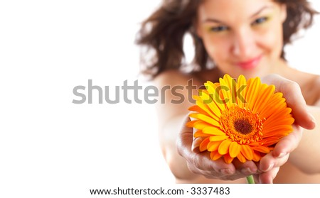 Beautiful angelic woman with flower in her hands - focus is on the flower - check out my portfolio for more pictures - stock photo