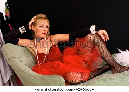 Beautiful angry looking woman as madam or prostitute, could also be a sexy elf or mrs. claus for christmas, looking directly at viewer.  Shot with blue and red strobes. - stock photo