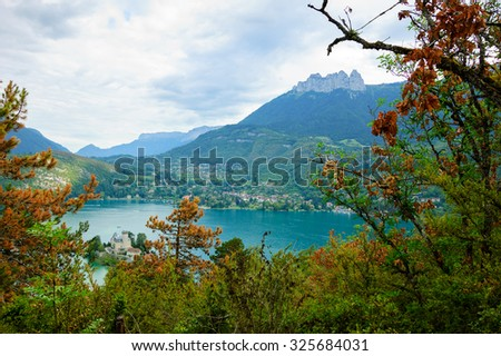 Beautiful Annecy lake (known as Europe's cleanest lake) with the castle seen through the trees in cloudy day. Haute-Savoie, France. - stock photo