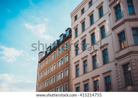 beautiful apartment houses with orange facades and blue sky - stock photo
