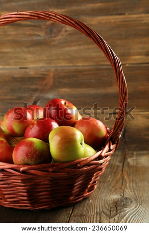 Beautiful apples in basket on brown wooden background