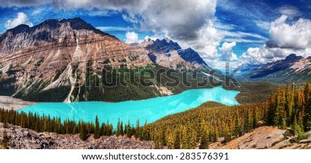 Beautiful aqua blue mountain lake settled amongst evergreen trees and majestic mountains - stock photo