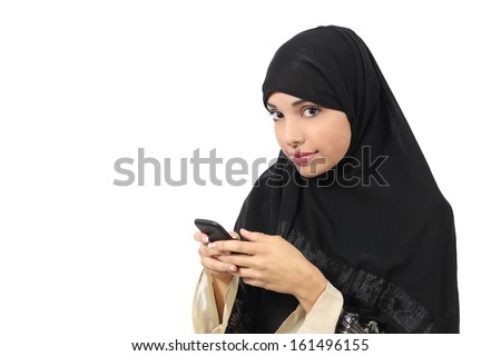 Beautiful arab woman browsing her smart phone and looking  to the camera isolated on a white background               - stock photo