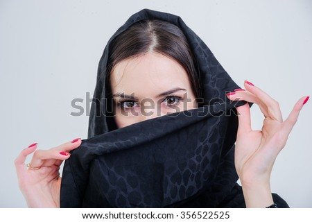 Beautiful arab woman looking forward isolated on grey background.  - stock photo