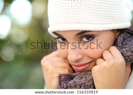 Beautiful arab woman portrait warmly clothed with an unfocused green background - stock photo