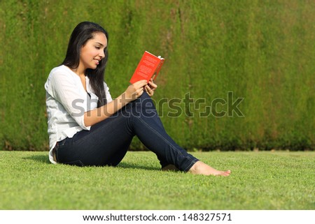 Beautiful arab woman reading a book sitting on the lawn of a park with a green background - stock photo