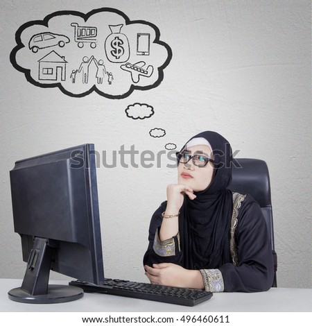 Beautiful Arabian businesswoman thinking her dream while sitting and daydreaming in front of computer