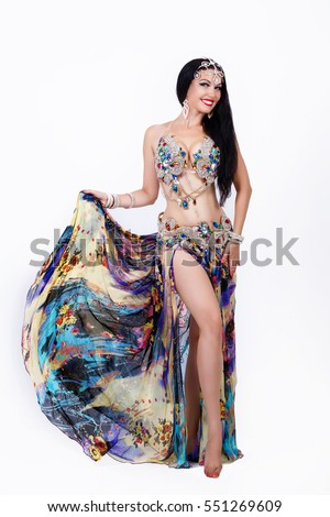Beautiful Arabic belly dancer harem woman in shaabi dress and jewelry dancing arms in air, isolated. Sexy oriental bellydance woman in traditional egyptian belly dance costume.