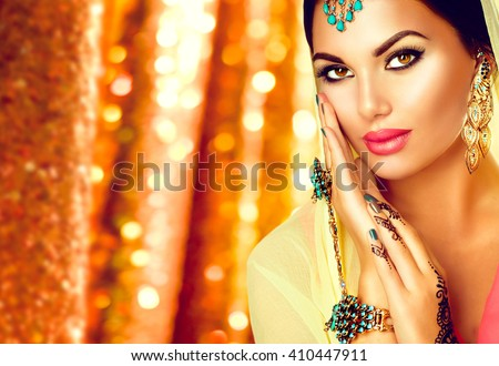 Beautiful Arabic girl portrait. Beauty young Arabian woman with menhdi, perfect make-up and accessories hiding her face behind a veil. Indian Bride. Arab Traditions and culture concept - stock photo