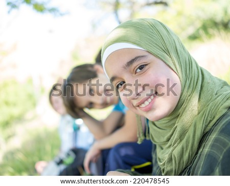 Beautiful Arabic girl with family enjoying in nature - stock photo