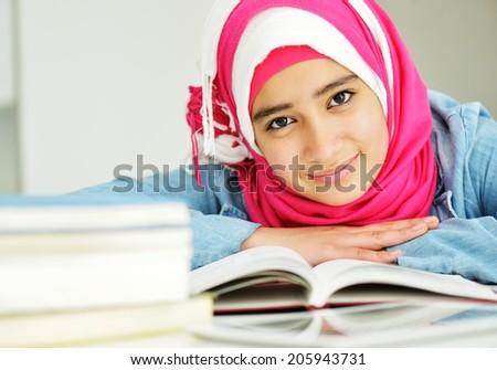 Beautiful Arabic Muslim girl reading on college - stock photo