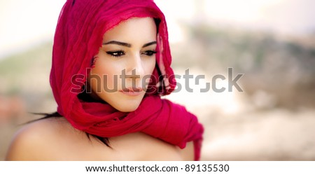 Beautiful Arabic woman wearing red scarf, stylish female portrait over soft natural background with copy space - stock photo