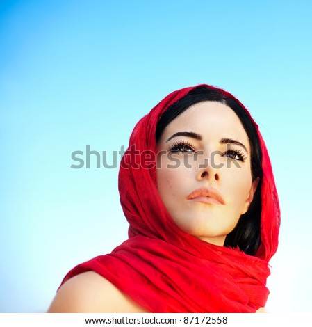 Beautiful arabic woman wearing red scarf, traditional muslim clothes, latest fashion design, stylish female portrait over blue natural background with copy space, soft focus - stock photo