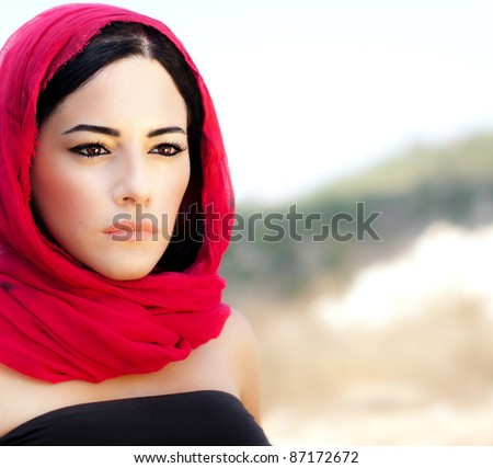 Beautiful arabic woman wearing red scarf, traditional muslim clothes, latest fashion design, stylish female portrait over soft natural background with copy space - stock photo