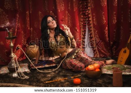Beautiful arabic woman with hookah in a harem - stock photo