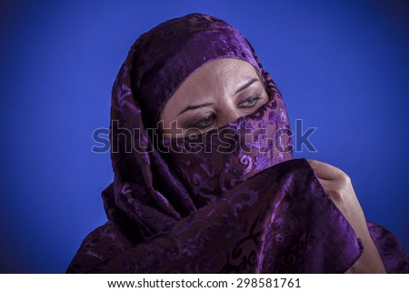 Beautiful arabic woman with traditional veil on her face, intense look - stock photo