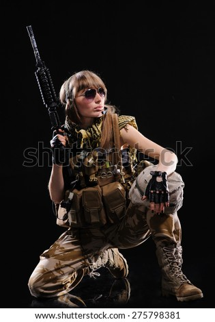 Beautiful army girl with gun isolated over black background - stock photo