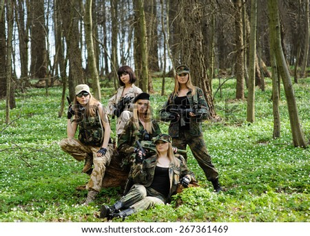 Beautiful army girl with gun  outdoor in the forest - stock photo