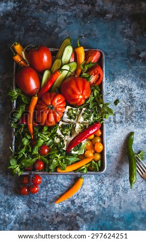 Beautiful arrangement of fresh vegetables served on oven sheet over on dark background. Include various colorful tomatoes, peppers, cucumber, green salad and cubes of cheese. Dark rustic styling - stock photo
