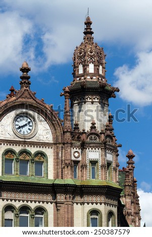 Beautiful Art Nouveau building with clocks in Hungary, in Budapest. Moldings, windows and details against the blue summer sky - stock photo