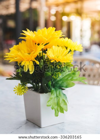 beautiful artificial yellow flower on table