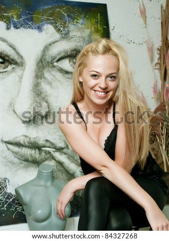 beautiful artist in the studio in front of her paint - stock photo