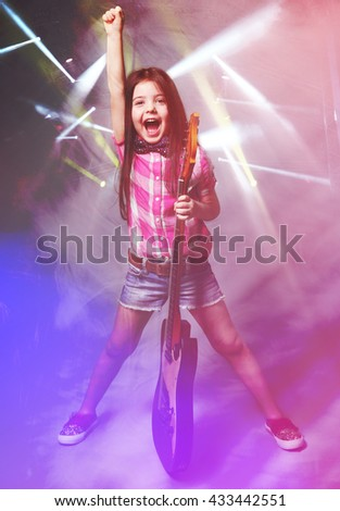 Beautiful artistic little girl playing guitar on laser rays background - stock photo
