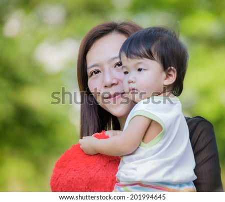 Beautiful asia Mother And Baby outdoors. Nature. Beauty Mum and her Child playing in Park together. Outdoor Portrait of happy family. Joy. Mom and Baby - stock photo