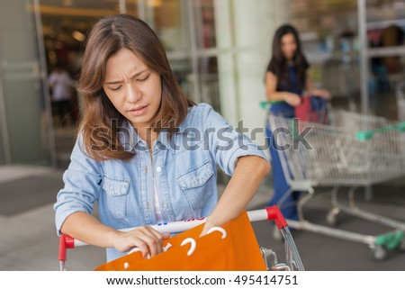 Beautiful Asia woman unhappy with bags in shopping center. (lens blur effect)
