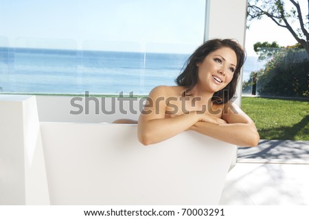 Beautiful Asian-American brunette model in modern bath tub in luxury bathroom with glass wall overlooking ocean. - stock photo