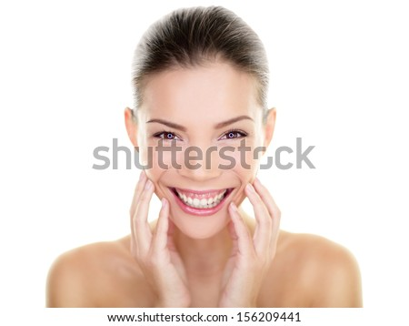 Beautiful Asian beauty woman touching perfect face skin laughing happy. Healthy skincare concept with candid smiling girl smiling at camera. Body care concept. Fresh mixed race Asian Caucasian, 20s. - stock photo