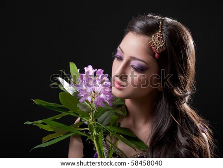 Beautiful asian bride holding purple flowers, isolated on black