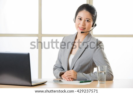 Beautiful asian business customer service woman smiling in office - stock photo