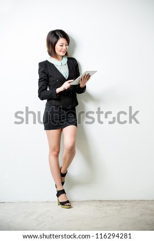 Beautiful Asian business woman reading her tablet computer. Full length shot, leaning against a white wall. - stock photo