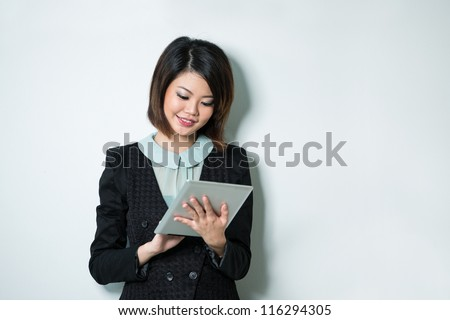 Beautiful Asian business woman reading tablet computer. - stock photo