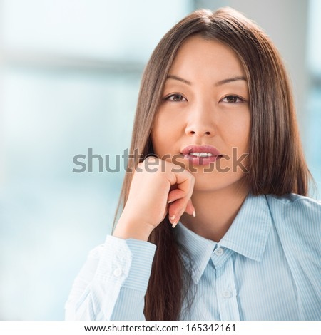 Beautiful asian business woman relaxing during a meeting at office with her colleagues - stock photo