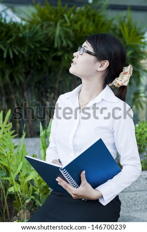 Beautiful Asian business woman sitting and take note in front of officer. - stock photo