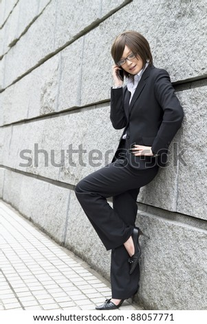 Beautiful asian business woman using a cellular phoen. - stock photo