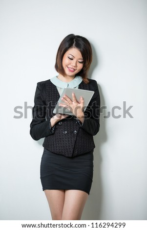 Beautiful Asian business woman using tablet computer. Leaning against a white wall. - stock photo